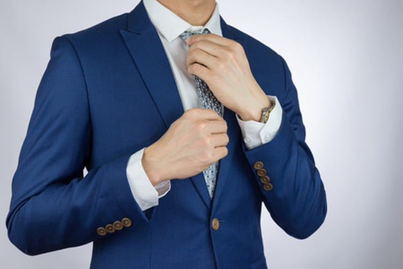 52532857 - businessman fitting up blue suit and necktie