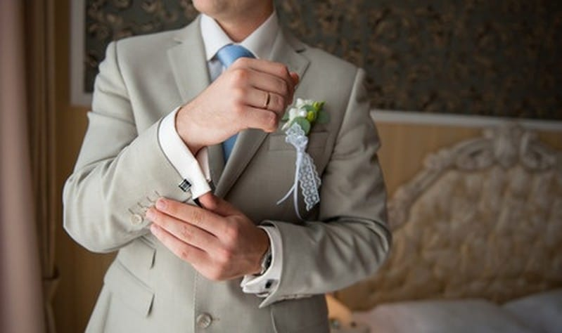 41763309 - groom in a suit, hands wear cufflinks.